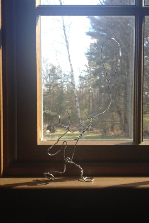 Figure of boy made of twisted wire in front of a window view of the forest.